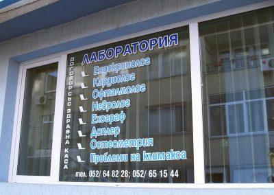 изрязани надписи от цветно фолио с бял контур на витрина на лаборатория